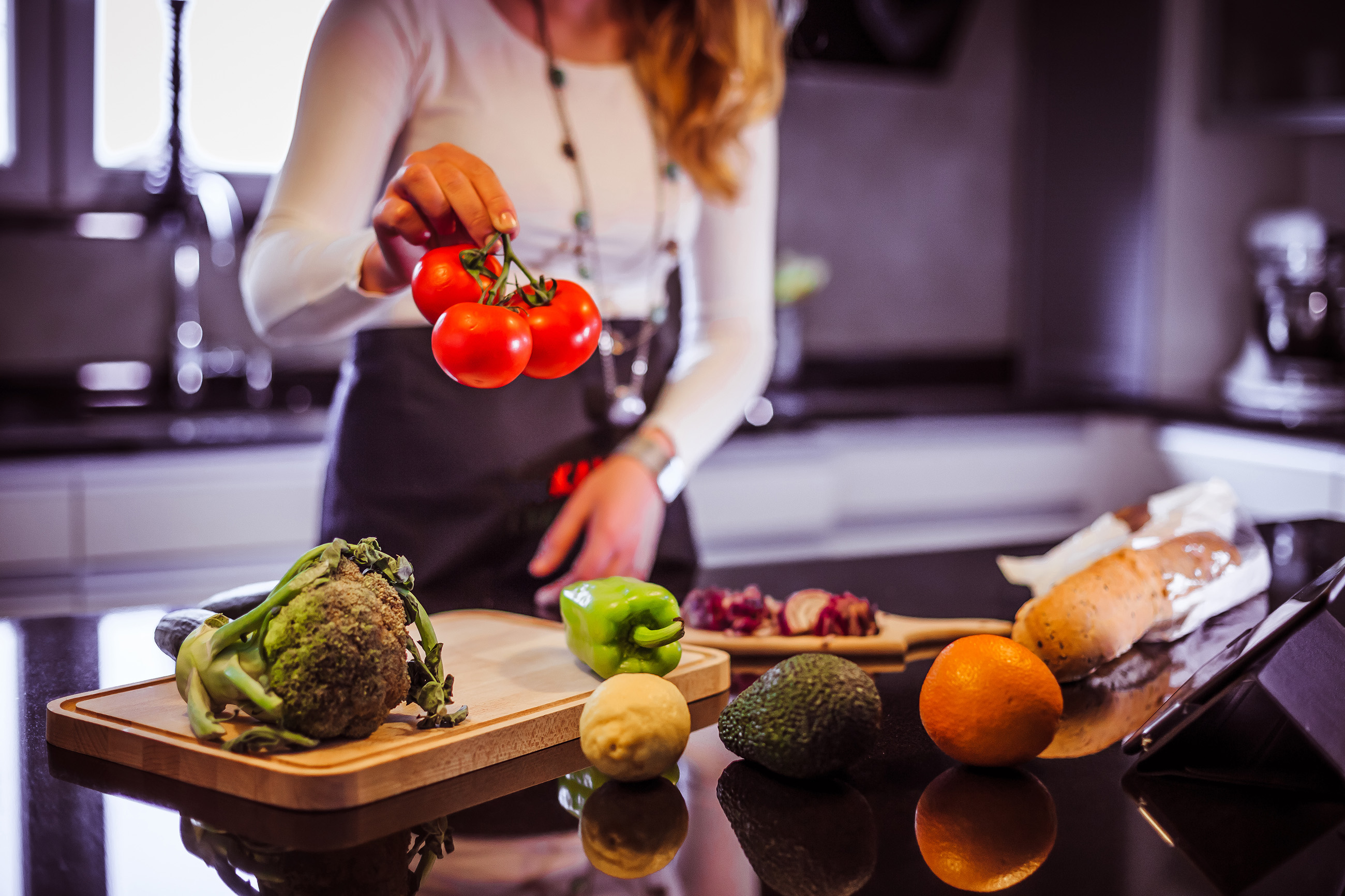 Young woman cooking healthy meal made of various vegetable and fruit